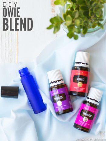 Bottles of Lavender, Melrose and Geranium Essential Oils next to a blue roller ball bottle. Text overlay DIY Owie Blend.