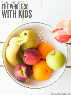 Assorted ripe fruit in a white colander on a vintage white wooden table. Text overlay How We Did the Whole 30 with kids.