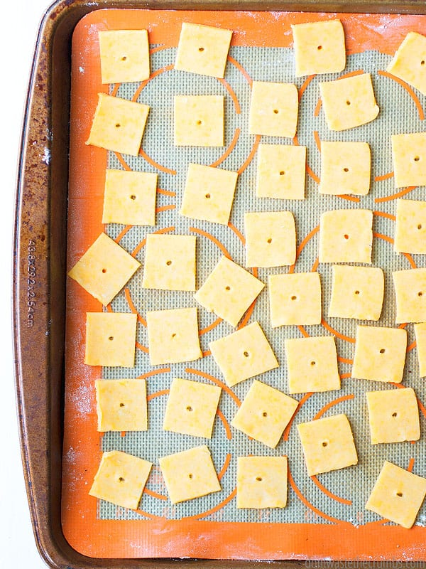 Round white bowl overflowing with Cheez-It like crackers. Text overlay Easy Homemade Cheez-Its.