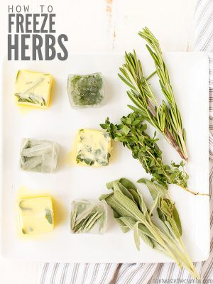 "Frozen herbs in cubes of olive oil and butter with fresh herbs laying on a cutting board. Text overlay says, ""How to Freeze Herbs""."