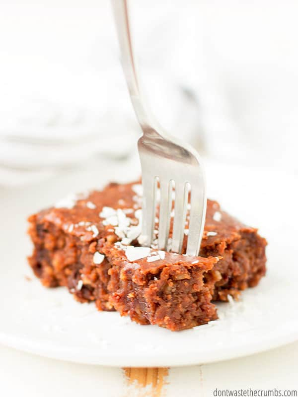 A piece of chocolate oatmeal cake on a plate with a fork taking a bite.