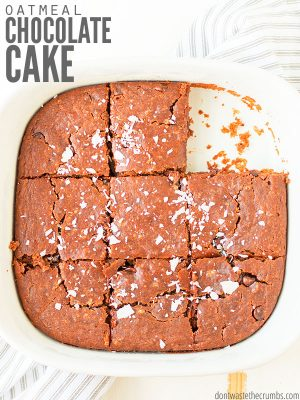 """A pan filled with chocolate cake cut into squares with text overlay, """"Oatmeal Chocolate Cake""""."""