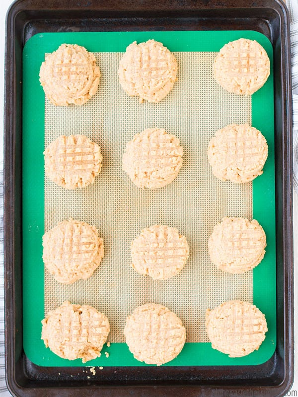 12 fork pressed cookies on a baking sheet and silicone mat. The photo is taken from a birds eye view and the cookies are about to be baked.