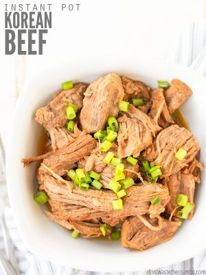 "Bowl of shredded korean beef with green onions sprinkled on top. Text overlay says, ""Instant Pot Korean Beef""."