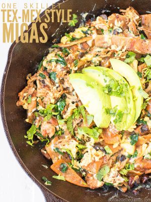 "Cast iron skillet with migas, topped with cilantro and sliced avocado. Text overlay says, ""One Skillet Tex-Mex Style Migas""."