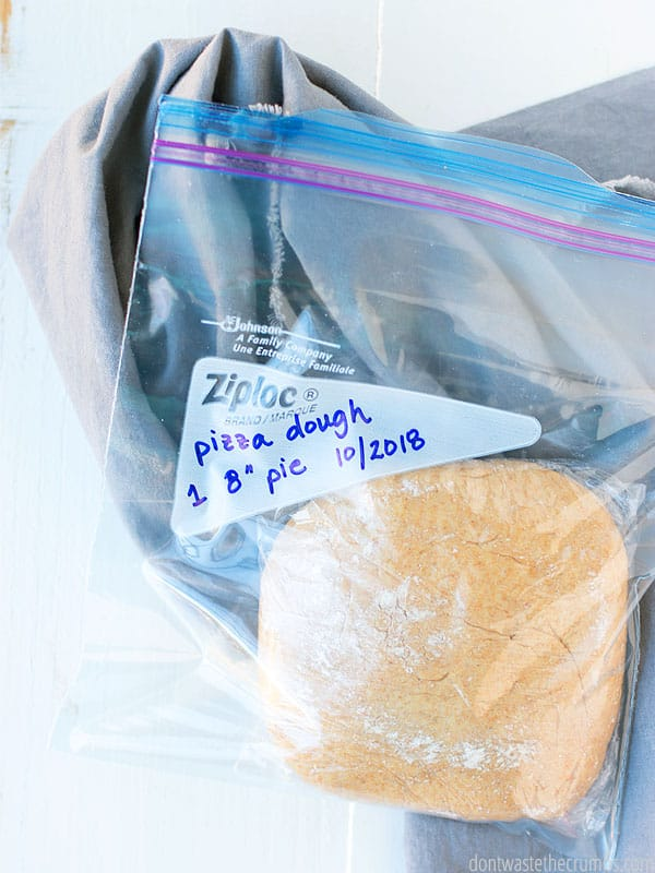 A ball of homemade pizza dough double wrapped in plastic wrap and a gallon size freezer bag. The writing on the label is dated and reads, pizza dough. Now you are ready to freeze pizza dough.