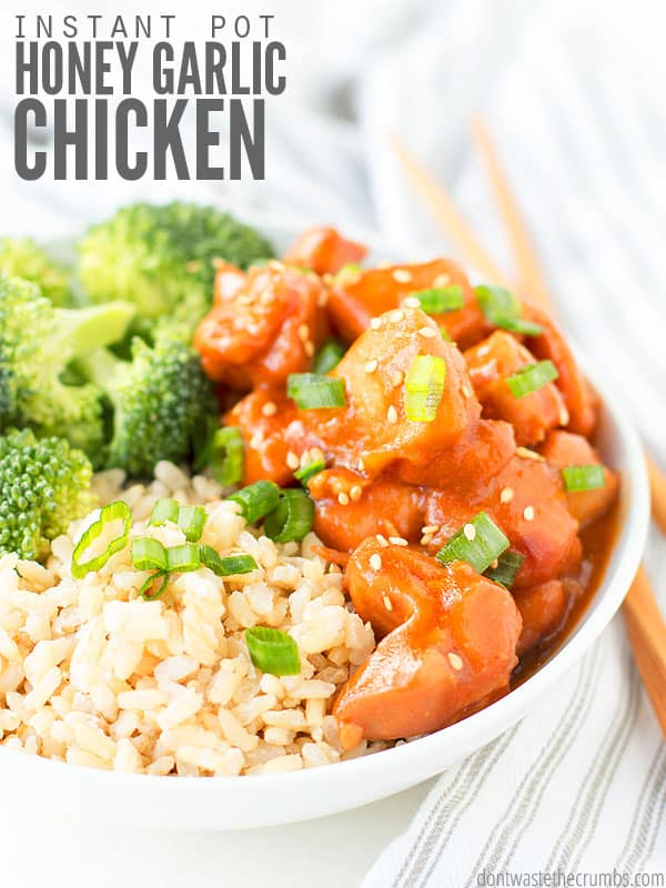 White bowl of hot rice, broccoli and chicken on a table with chopsticks. Text overlay Instant Pot Honey Garlic Chicken