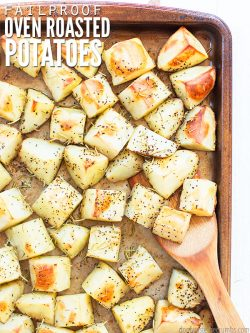 "Sheet pan with roasted potatoes seasoned with herbs and a wooden spoon taking a scoop. Text overlay says, ""Failproof Oven Roasted Potatoes""."