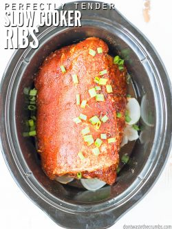 Black slow cooker pot with rack of pork ribs and dry rub. Text overlay Perfect Tender Slow Cooker Ribs.