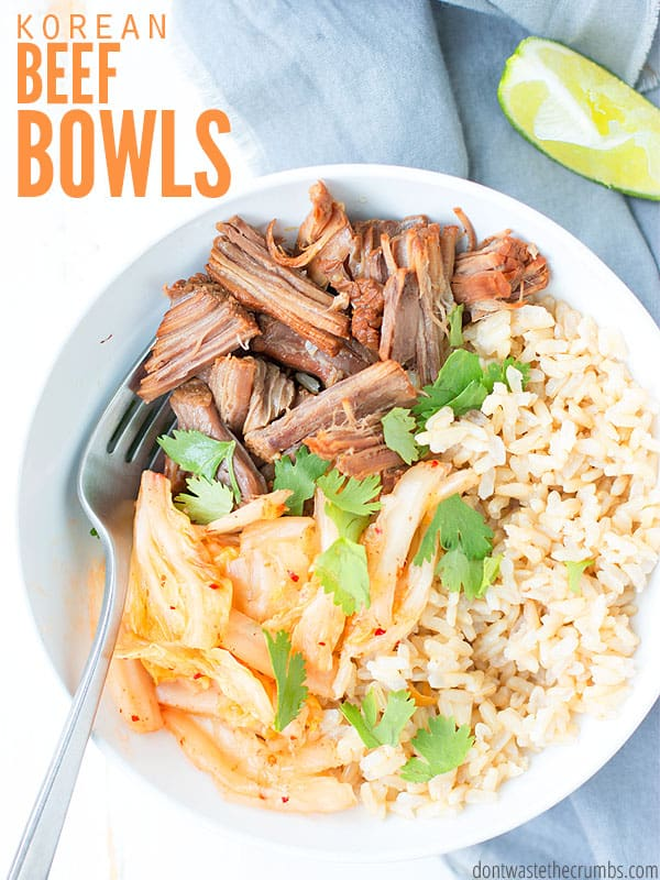 White bowl filled with rice, shredded beef, kimchi and garnished with cilantro, with a sliced lime wedge on a gray kitchen towel. Text overlay Korean Beef Bowls.