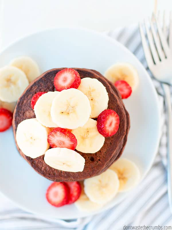 Vertical shot of a stack of chocolate pancakes, topped with sliced strawberries and bananas.