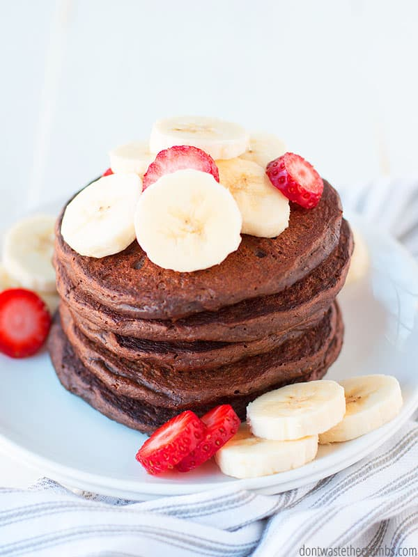 Tall stack of chocolate pancakes on a plate, topped with sliced bananas and strawberries.