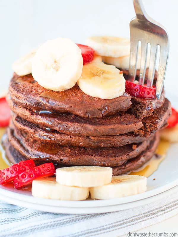 Tall stack of chocolate pancakes topped with sliced bananas and strawberries with a fork grabbing a bite.