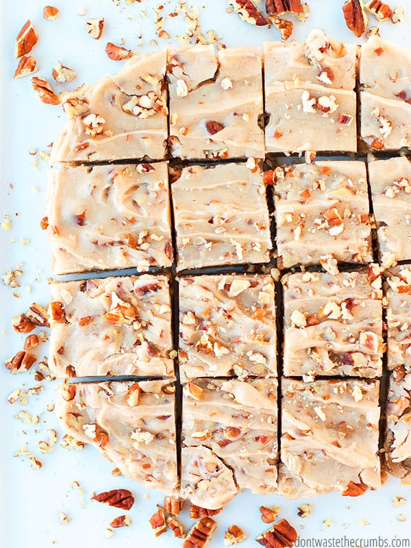 Maple pecan blondies topped with chopped pecans and cut into squares.
