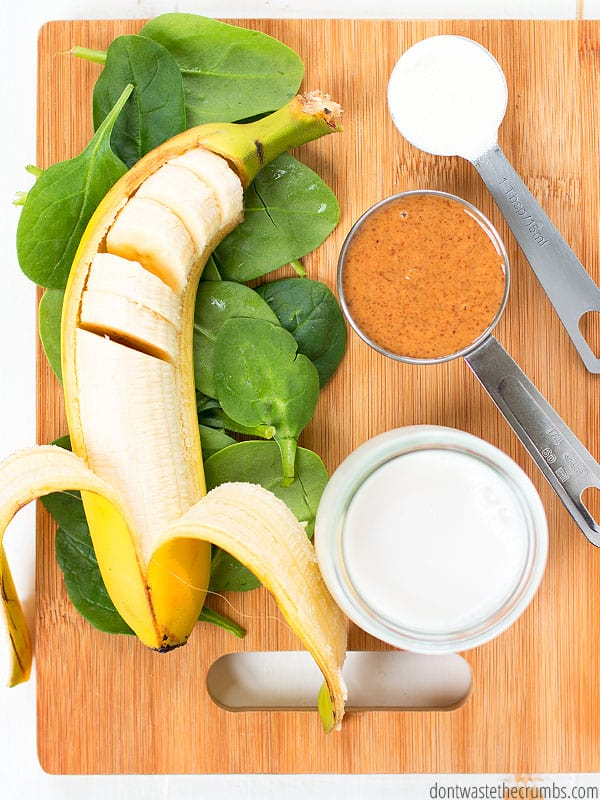 Green smoothie ingredients with banana, spinach, nut butter and milk