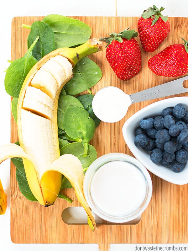 Green smoothie ingredients with banana, spinach, milk, strawberries, blueberries, and collagen