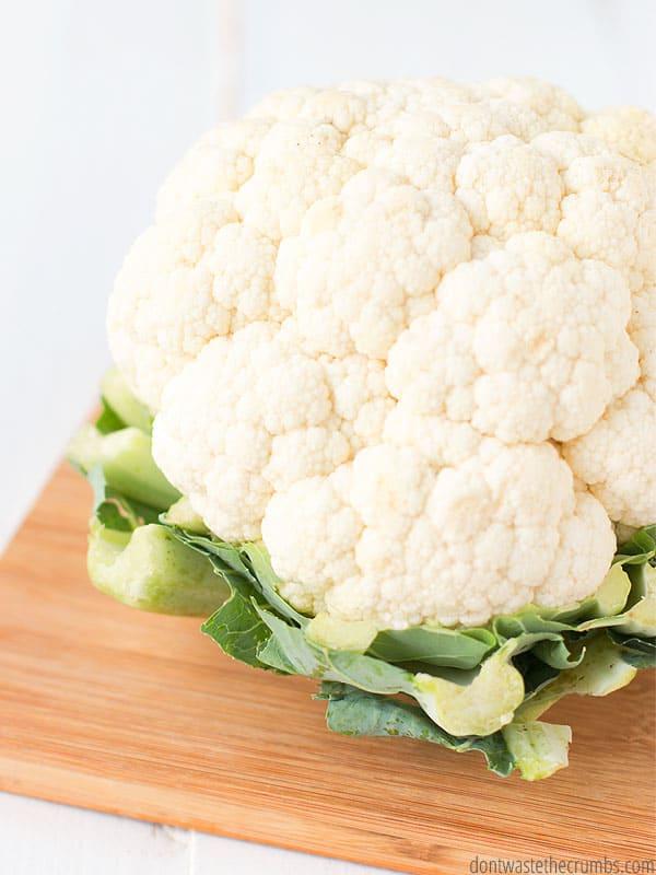 head of cauliflower on a wooden cutting board
