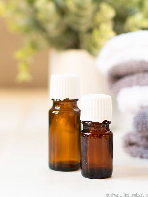 Two bottles of essential oils sitting next to a stack of towels.