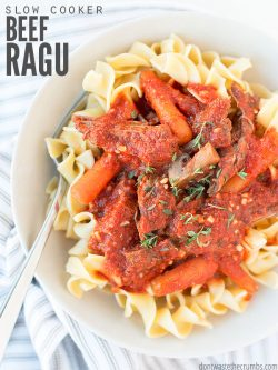 "Bowl of pasta topped with beef ragu, baby carrots and herbs. Text overlay says, ""Slow Cooker Beef Ragu""."