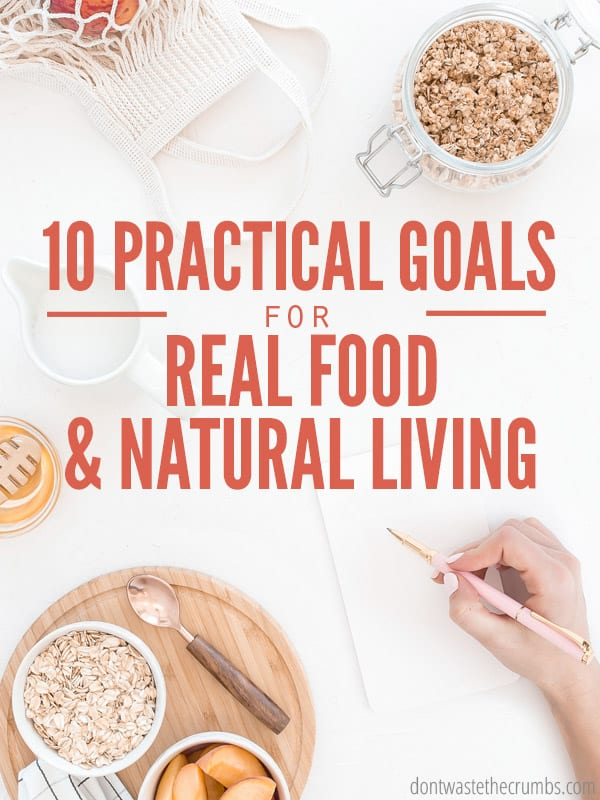 "Different healthy food items on a table and a women's hand holding a pen hovering over a piece of paper ready to take notes. Text overlay says, ""10 Practical Goals for Real Food & Natural Living""."