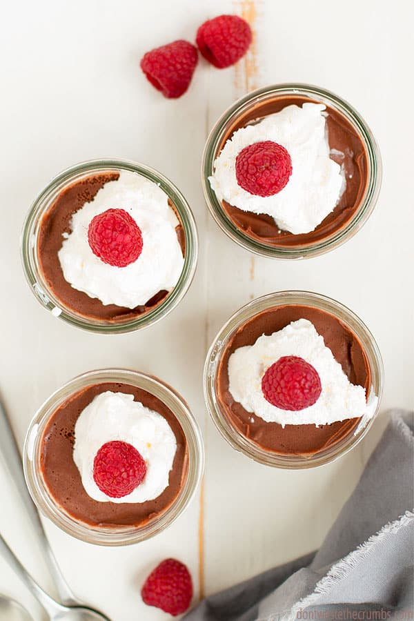 Homemade chocolate pudding in four mason jars, from the top. They are topped with whipped cream and raspberries. There are three raspberries spread on the table around the jars.