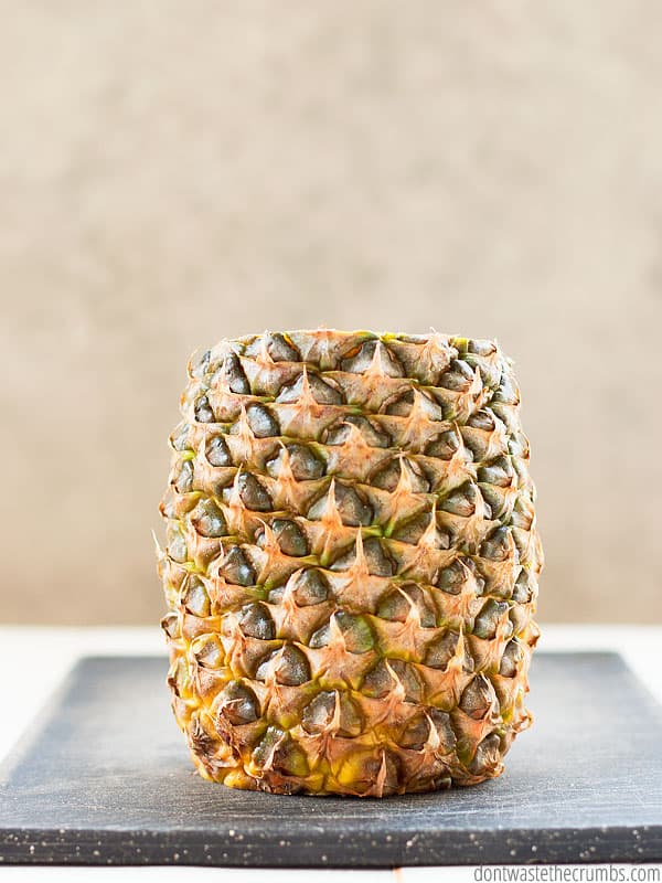 A fresh pineapple with top and bottom cut off. Standing upright on a black cutting board.