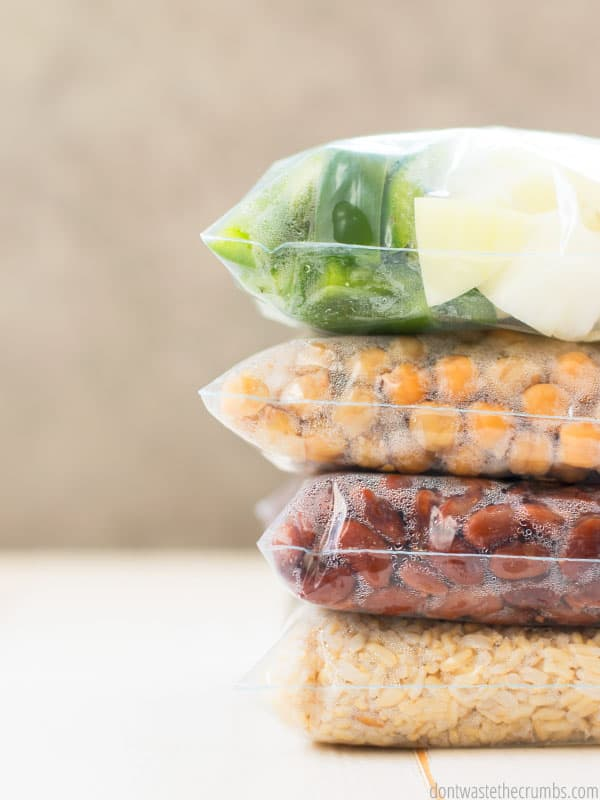 Four Bags of Freezer Cooking prepped food, stacked on top of each other. Food include green peppers and onion, garbanzo beans, pinto beans, and brown rice.