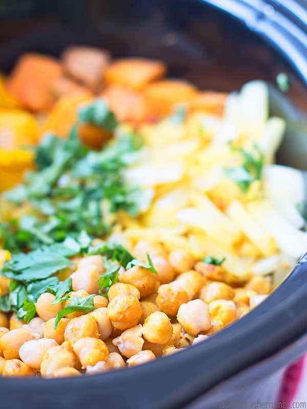Thai Pineapple Vegetable Curry in the slow cooker, with chickpeas, onions, pineapple, cilantro, sweet potato, and peppers.