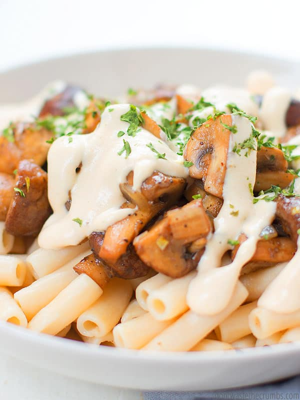 Creamy Mushroom pasta, from the top, mushrooms on top of pasta, drizzled with creamy sauce, sprinkled with green herbs.