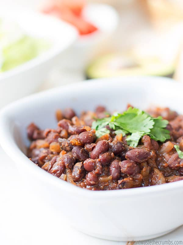 Spicy Citrus Black Beans in a bowl, topped with cilantro. Ready to eat with a rice and beans meal.