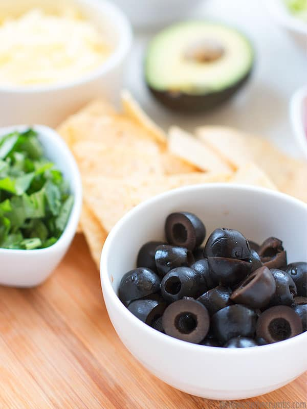 Toppings for a Rice and Beans dinner, chopped olives, cilantro, tortillas chips, shredded cheese and avocado.