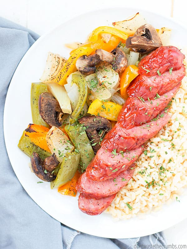 Roasted vegetables with sausages, sheet pan sausage and peppers with onions and mushrooms recipe served with rice.