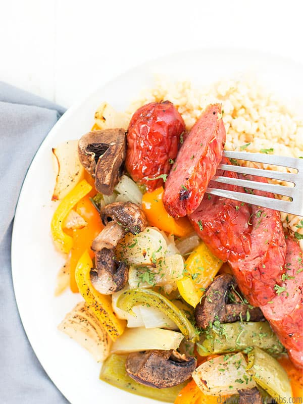 Sausage and peppers sheet pan dinner with onions and mushrooms served on brown rice, with a fork picking up a piece of sausage.