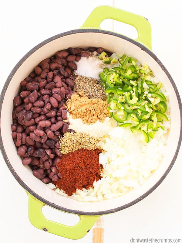 Cooked black beans recipe in a bowl with spices like chili powder, garlic, salt, oregano, cumin, and sage. The beans are covered with chopped jalepeno and onions.