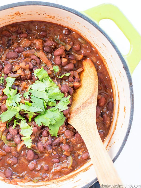 These Spicy Citrus black beans in a large pot, sprinkled with cilantro with a wooden spoon stirring.