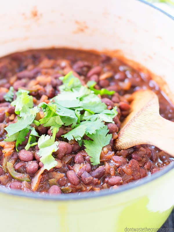 Spicy Citrus black beans in a large pot, sprinkled with cilantro with a wooden spoon inside the pot.