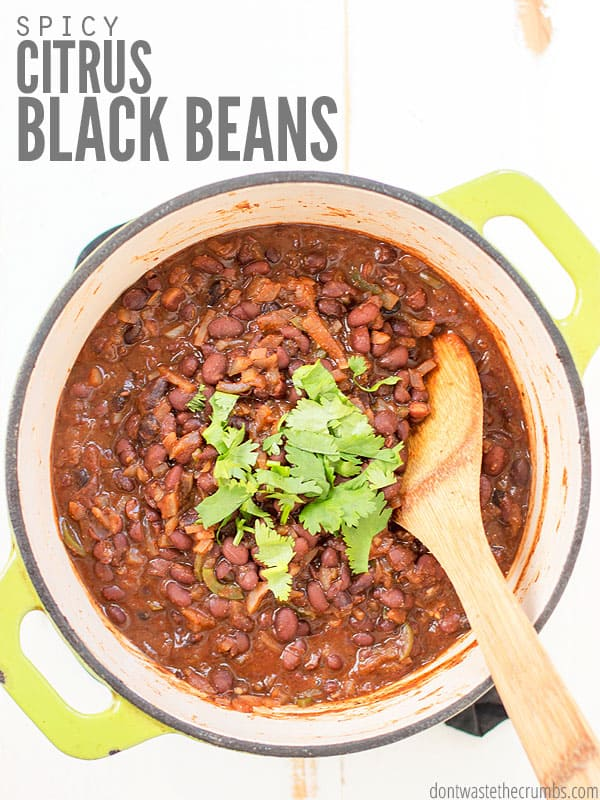 """Cooked Black beans in a large pot. A wooden spoon is in the beans, and it is sprinkled with cilantro. Text overlay says, """"Spicy Citrus Black Beans."""""""