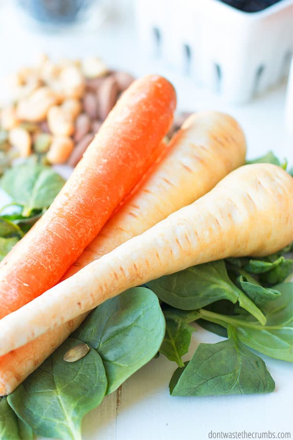 Ways to save money with grocery shopping. Image shows carrots and parsnips on spinach.