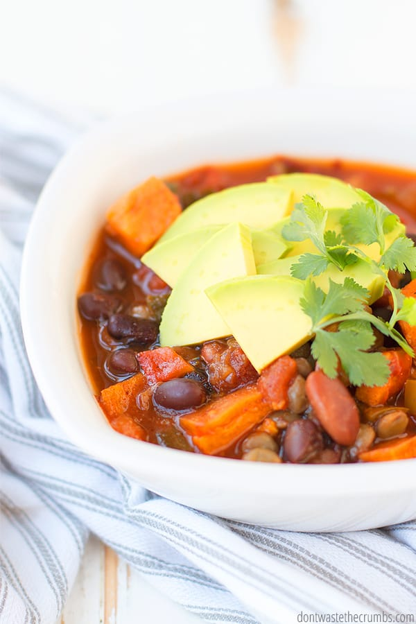 This Instant Pot Vegetarian Chili is easily made in a slow cooker! With sweet potatoes, beans, peppers, and spices, it's perfect for fall chilly nights! Top with fresh cilantro and avocado for a fresh and creamy finish!