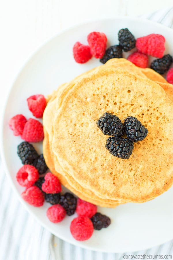 View of a stack of fresh sourdough pancakes from above. There are many raspberries and blackberries sprinkled on the plate.