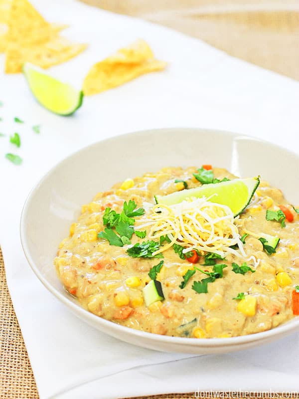 This slow cooker chicken chili is so creamy and delicious. Plus the vegetables add texture and nutrition. Try it with all of the yummy toppings like cilantro, avocado, lime and tortilla chips! ::dontwastethecrumbs.com