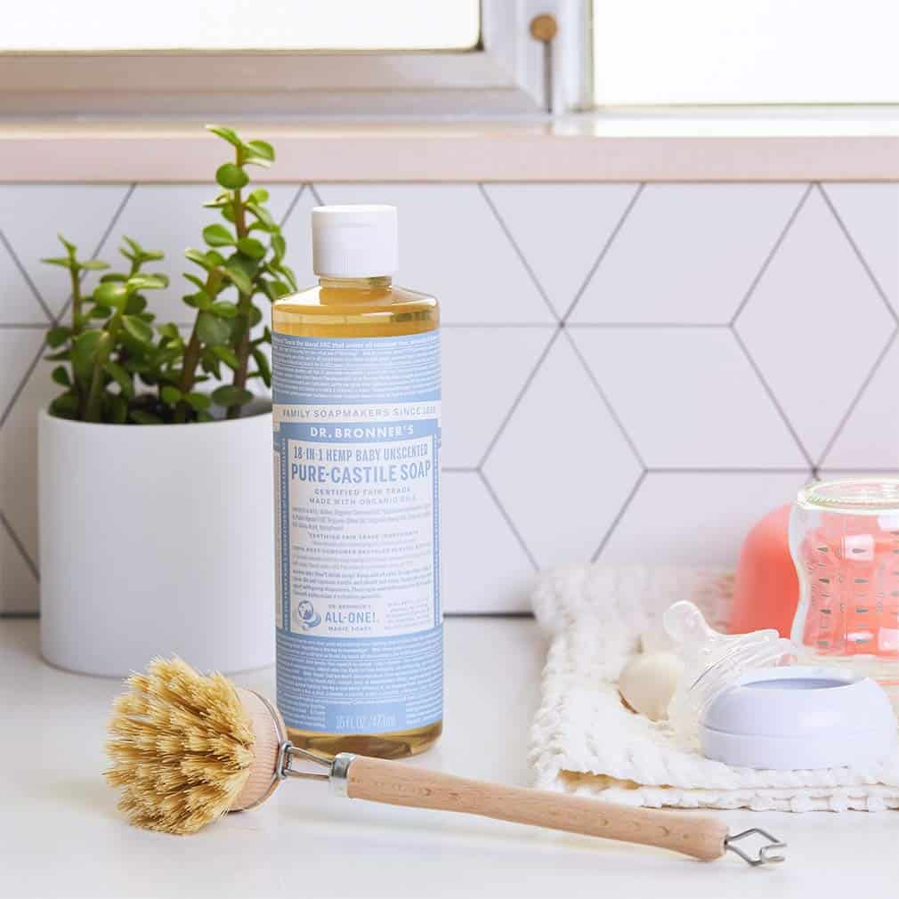 A bottle of Dr. Bronner's Pure Castille Soap sits on a counter next to a bottle brush and baby bottles and nipples.