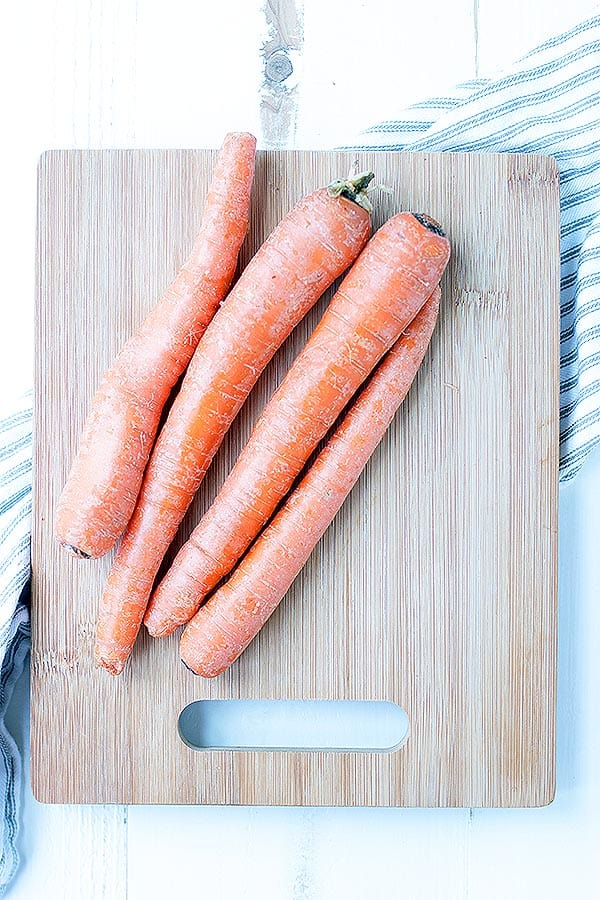 Four unpeeled, untrimmed, large carrots sit on top of a wooden cutting board.