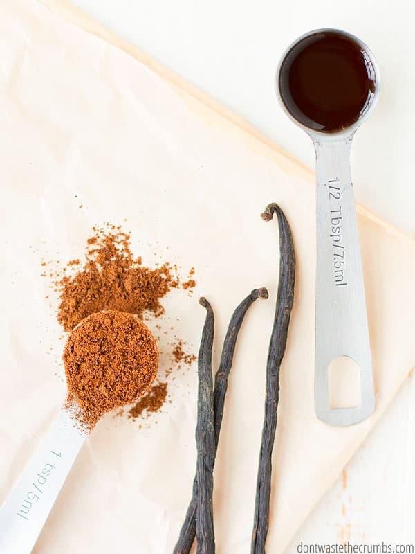 A casually laid out assortment of vanilla  products including vanilla bean powder on the right, The tops of three vanilla beans in the middle, and a measuring spoon of vanilla extract on the right.