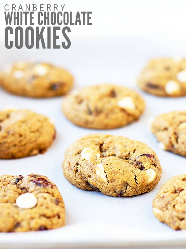 The cover photo to the cranberry white chocolate chip cookies. It shows 8 freshly baked cookies on a piece of parchment paper.