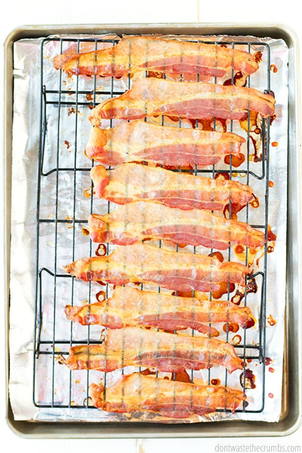 A birds Eye view of the golden brown, crispy, and delicious bacon sitting on a wire rack. The rack has both tin foil and a rimmed cookie sheet beneath it.