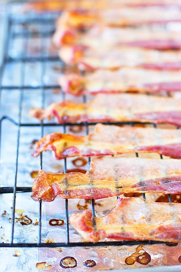 The cooked edges of the bacon that are cooling on the wire rack which is still placed on the tin foil and in the rimmed cookie sheet.