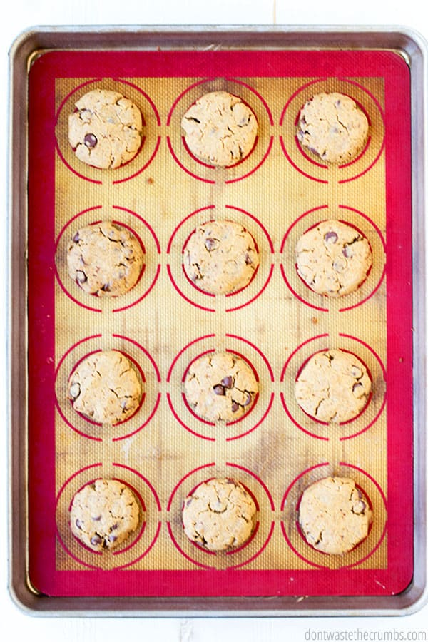 12 scoops of pressed dough on a silicone mat that is laid on top of a baking sheet.