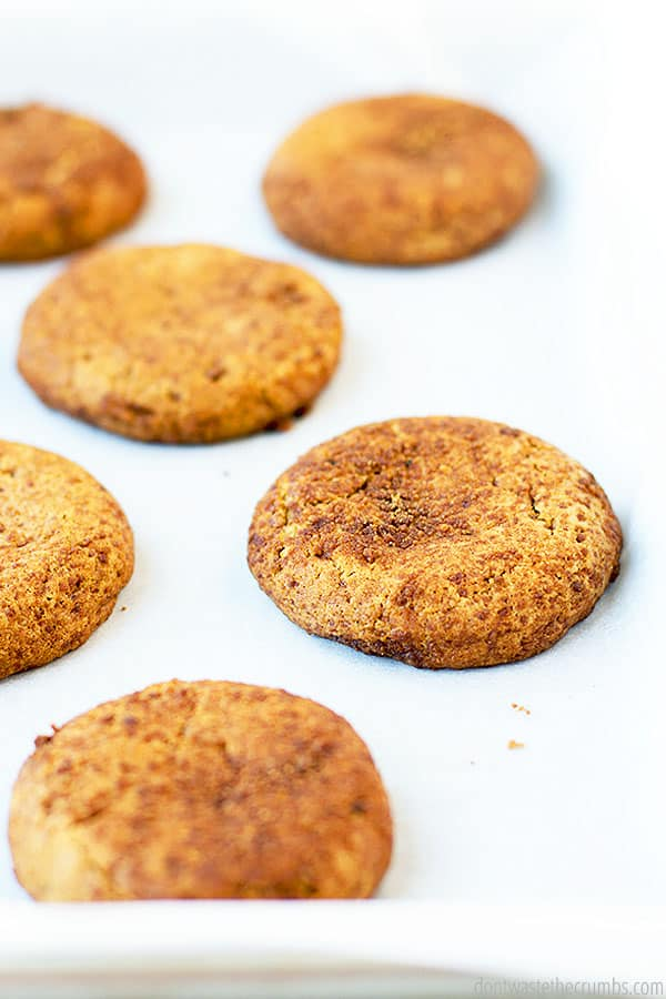 Six crispy outer and moist centered snickerdoodle cookies laying on top of parchment paper and a baking sheet.