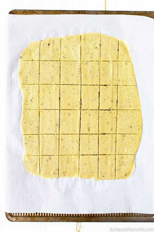 This cracker recipe requires no kneading! Just spread the cracker dough onto a parchment lined baking tray, score the dough, and bake. Makes about 36 crackers.